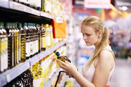 aceite de oliva: Mujer rubia joven que escoge una botella de aceite de oliva de los estantes de un supermercado y la lectura de la etiqueta