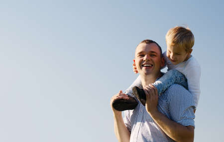 shoulder ride: Young father giving his son a piggy back ride as the youngster sits on his shoulders laughing with enjoyment, low angle against a blue sky with copyspace
