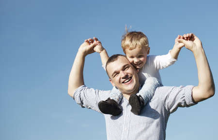 shoulder ride: Dad giving his young son a piggy back ride as they both laugh with pleasure and enjoyment, low angle against a clear blue summer sky with copyspace Stock Photo