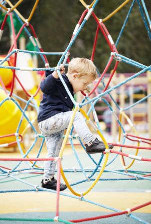 playground children: Ni�o peque�o feliz que sube en el equipo del patio mientras disfruta de la aventura y el ejercicio