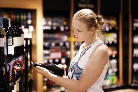 booze: Woman shopping for wine or other alcohol in a bottle store standing in front of shelves full of bottles and holding bottle in her hand and reading inscription Stock Photo