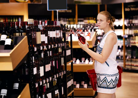 Woman shopping for wine or other alcohol in a bottle store standing in front of shelves full of bottles with a serious expression as she tries to make up her mind Фото со стока