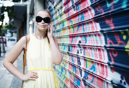 Woman in sunglasses chatting on a mobile phone while standing alongside a wall covered in colourful graffiti or a mural