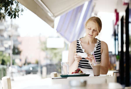 taking a break: Attractive woman taking picture of a pastry on her smart phone as she sits at a table at an open-air restaurant enjoying refreshments Stock Photo