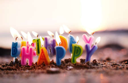 Colourful birthday candles spelling out the alphabet letters - Happy Birthday - standing upright in beach sand burning on a seashore at the edge of the sea