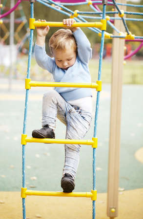 jungle gym: Cute little boy climbing on a the metal bars of a jungle gym in a childs playground