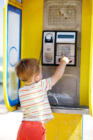 Young boy talking to the phone in a yellow telephone booth photo