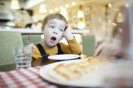 어린 소년 하품 그는 그의 앞에 빈 접시로 식탁에 앉아 먹이를 기다립니다