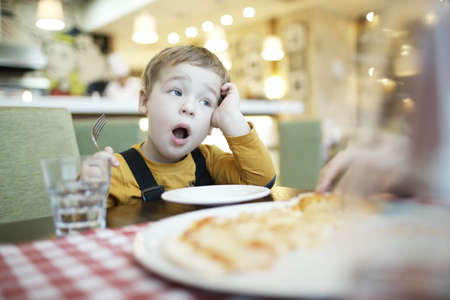 childhood obesity: Young boy yawning as he waits to be fed sitting at the dining table with an empty plate in front of him