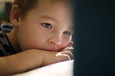 Little boy watching cartoons on touchpad being sad Stock Photo - 27068701