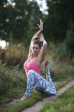 Supple graceful young woman exercising outdoors on a rural track posing on one knee with her hands held above her head