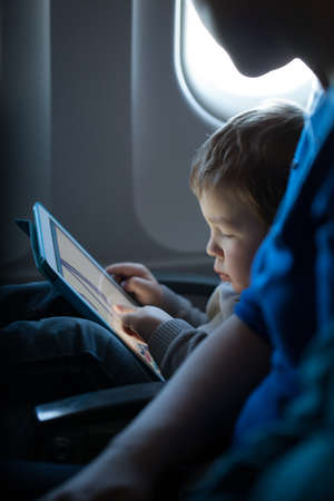 Little boy sitting in his seat during a flight playing contentedly with a tablet computer in an airplane watched by his mother