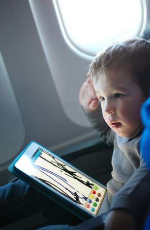 Little boy sitting in his seat during a flight and painting on a tablet computer in an airplane photo