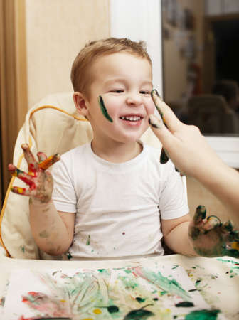 daubs: Happy little boy doing finger painting sitting with his hands full of colorful paint in front of a sheet of paper with paint daubs laughing as his mother dabs his face with paint