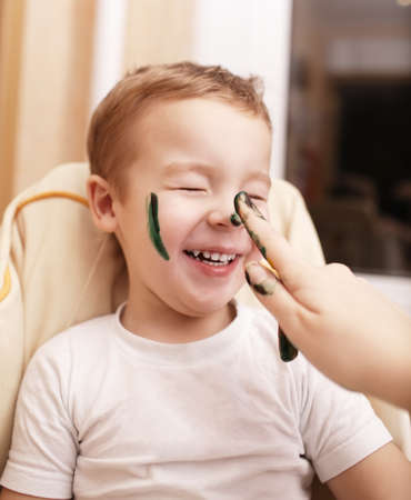 streaking: Little boy laughing as his mother paints his face streaking his cheek and dabbing his nose with black face paint Stock Photo