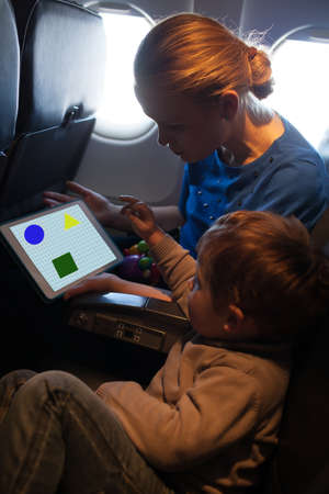 Young mother and son traveling on an aeroplane playing together on a tablet computer to amuse the young child photo
