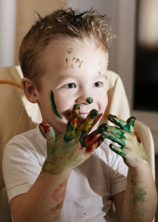 daubs: Excited handsome little boy playing with finger paints laughing as he holds up his hands full of colorful paint daubs Stock Photo