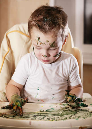concentrates: Creative little boy playing with finger paint creating a swirling pattern as he concentrates on his work