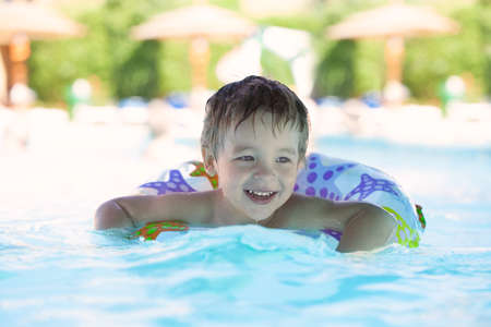 Kid learns to swim using a plastic water ring in the swimming pool or waterpark photo