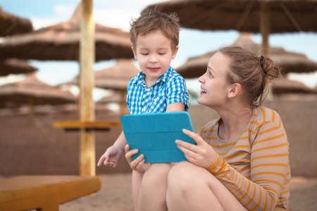 Little boy with his mother at a beach resort playing with a tablet computer on the beach under straw beach umbrellas photo