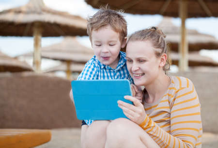 Happy mother and her small son at a beach resort playing on a tablet computer together under beach umbrellas at the seaside Фото со стока - 27069116