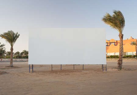 Blank white billboard with copyspace for your advertisement or movie flanked by two palm trees photo