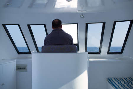 Man navigating a boat sitting in the captains chair during a cruise overlooking the ocean ahead, view from behind photo