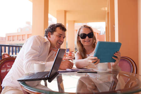 Young couple relaxing over coffee on a balcony sitting at a glass table smiling as they lean close together to read the screen on a tablet computer