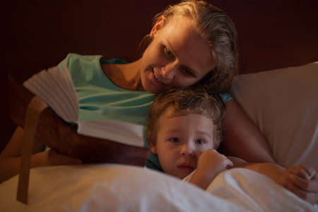 bed time: Mother reading a bedtime story to her little son cuddling down alongside him on the bed as he peers over the counterpane at the camera