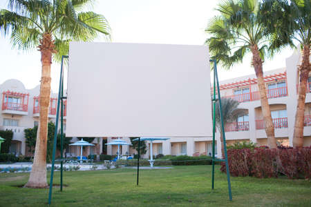 Blank billboard with tropical palm trees standing on a green lawn in front of an apartment block or resort accommodation photo