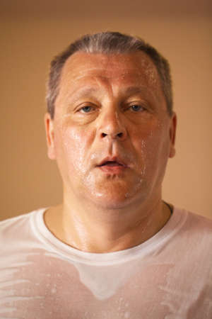 perspiring: Tired looking hot perspiring middle-aged man after a workout, closeup head and shoulders portrait looking directly at the camera