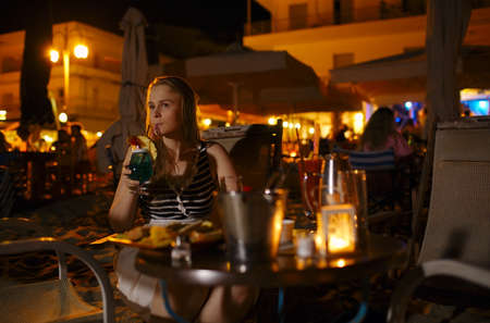 Young woman enjoying a drink in a pub or restaurant sitting at a table alone outdoors illuminated by electric lamps sipping a drink photo