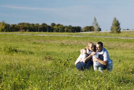Mother, father and their little son having fun in the countryside. Son hugs and kissing his father and mother as they laugh and frolic enjoying the fresh air and sunshine photo