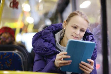 버스에 타는 동안 그녀의 터치 패드를 사용하여 보라색 재킷에 젊은 여자