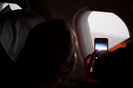 illuminator: Woman taking photographs through a cabin porthole with her mobile phone during a flight on an aeroplane