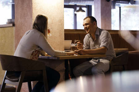 clang: Young couple in a cafe having dinner and talking.
