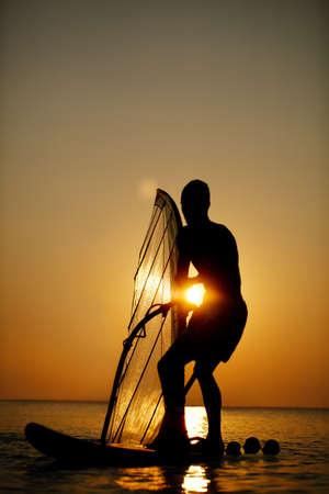 windsurf: Sailboarding Hombre en la puesta del sol en silueta contra el orbe brillante del sol en un cielo anaranjado colorido en un mar en calma