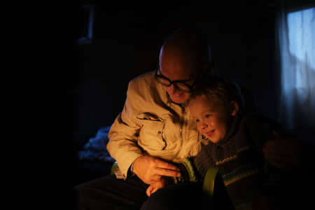 Grandfather hugs his grandson near fireplace at home with fire enlighting their faces. They are smiling photo