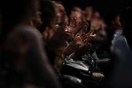 aplaudiendo: Vea abajo de una fila de personas que se sientan en una audiencia de personas que aplauden sus manos en agradecimiento por una actuación