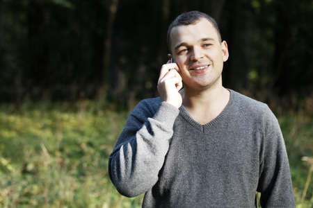 chats: Man laughing as he chats on his mobile phone while standing outdoors in a lush green park with copyspace