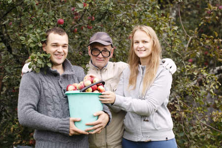 fruitage: Husband, wife and grandfather with fruitage. Man holding full bucket of fresh apples, woman putting some fruit on the top, all looking to the photographer Stock Photo
