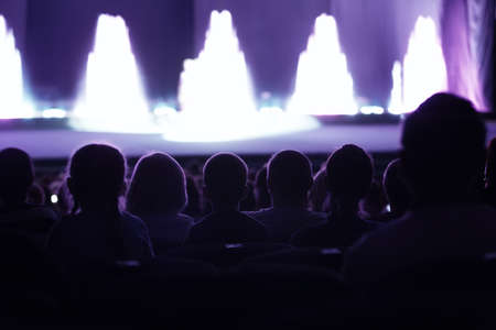 theater audience: Audience seated in an auditorium or theatre watching a live performance on stage with performers appearing as bright areas of light