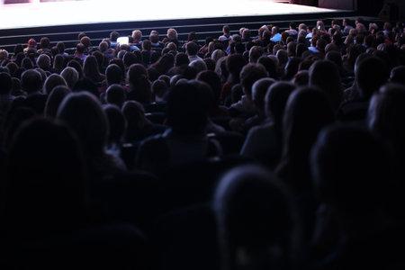 무대에서 라이브 공연을 관람하는 관중석에 앉아있는 사람들과 함께 포장 된 강당이나 극장의 뒤쪽에서 봅니다.