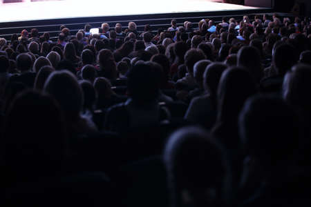 Uitzicht vanaf de achterkant van een volle zaal of theater met mensen zitten in een publiek kijken naar een live optreden op een podium
