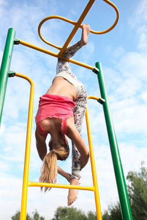 Athletic young blond gymnast working out on colourful metal bars in an outdoor playground hanging gracefully from one leg while stretching down with her other foot against a cloudy blue sky photo