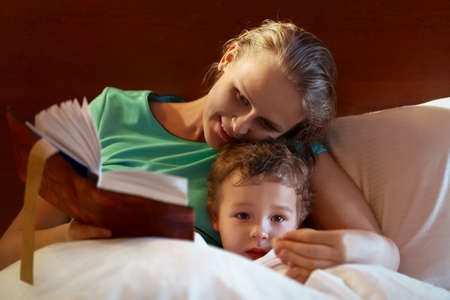 tells: Young mother reading from a thick book to her child in bed smiling as she tells the story as the child peers over the bedclothes at the camera with a serious expression