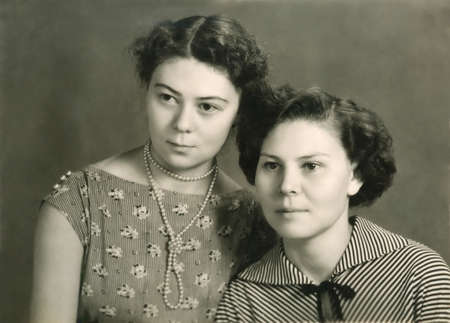 two generation family: Vintage sepia toned portrait of two attractive young women posing close together looking off to the side of the frame with serious expressions