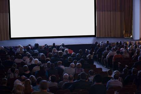 Publiek gezeten in de voorkant van een leeg podium met een leeg wit scherm in een verduisterde zaal, hoge hoek bekijken