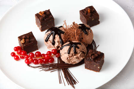 chocolaty: Scoops of creamy chocolate ice cream served with chocolate bonbons and a bunch of fresh red currants garnished with chocolate strands for a gourmet dessert