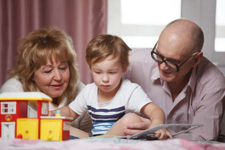 Happy grandparents spending time with their cute grandson playing with puzzle book photo